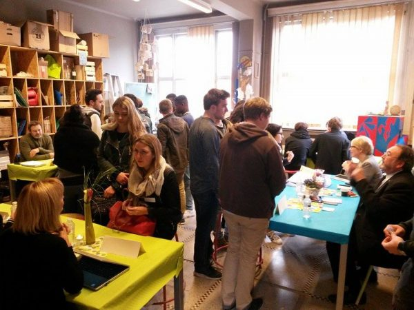 Photo de la précédente édition: élèves devant des tables discutant avec des entrepreneurs